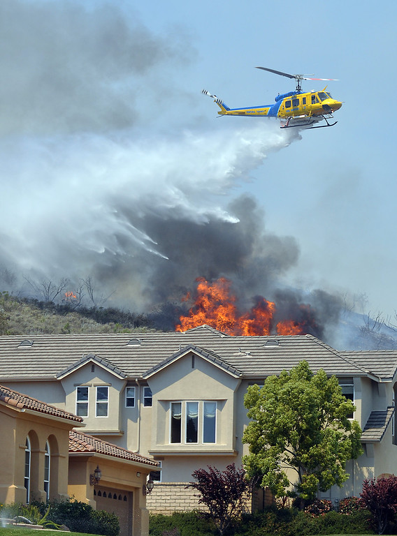 . A hillside in Newbury Park burns close to homes.  The fire started after 6 a.m. and grew to more than 6,500 acres by 2 p.m.  Photo by Tina Burch