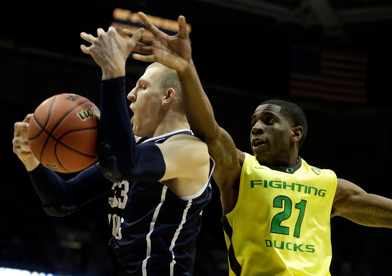 . BYU forward Nate Austin (33) battle for a rebound against Oregon guard Damyean Dotson (21) during the first half of a second-round game in the NCAA college basketball tournament Thursday, March 20, 2014, in Milwaukee. (AP Photo/Morry Gash)