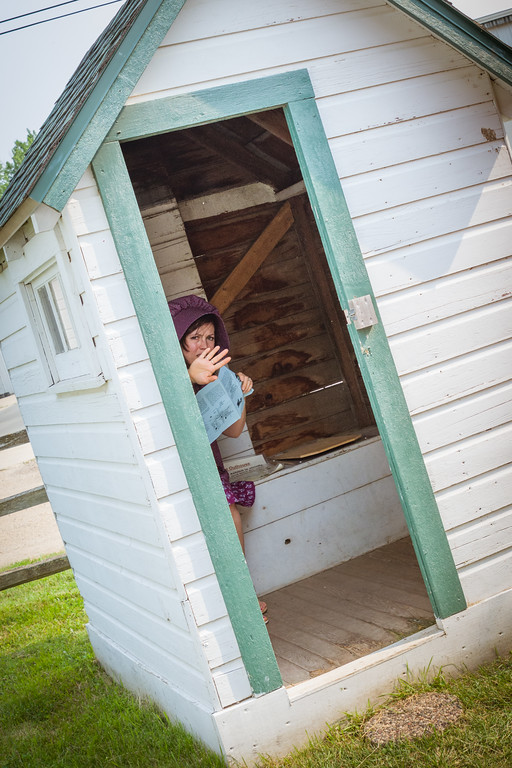 Becky, reading a brochure, waves me away from the open door as she sits inside the outhouse (which was all staged!)