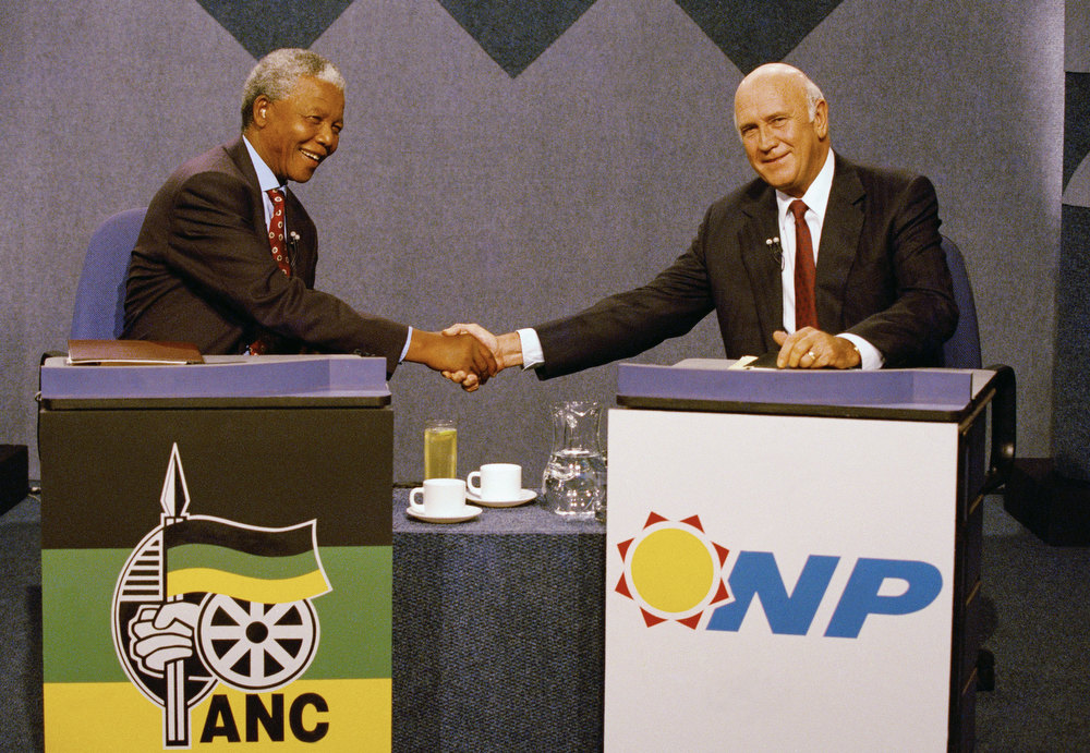 Description of . African National Congress President Nelson Mandela, left, and South African President F.W. de Klerk, shake hands prior to a television debate in Johannesburg, on Thursday, April 14, 1994, which was televised internationally. (AP Photo/John Parkin/Pool)