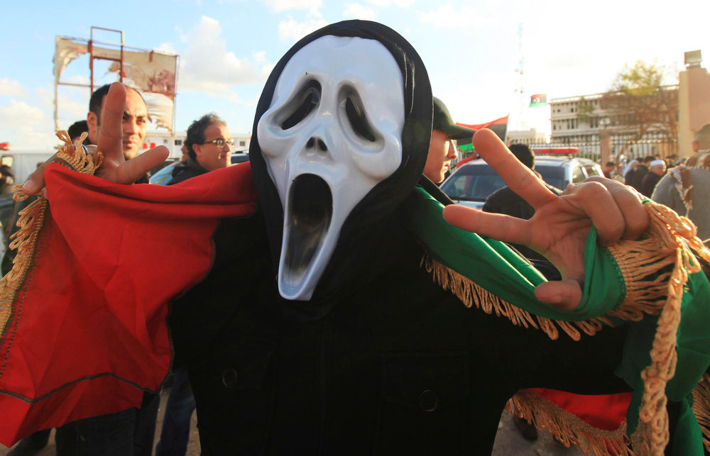 Description of . A reveler wearing a ghost mask gestures as thousands take to the streets to mark two years since the start of the country's revolution, in Benghazi February 15, 2013. The actual anniversary of the start of the revolt is not until Sunday, but celebrations began on Friday in remembrance of the arrest of a human rights lawyer that kindled the unrest. Cars flying national flags and blasting national songs honked their way through heavy traffic towards the courthouse, where about 2,000 were gathered, chanting anti-government slogans in between celebratory songs and speeches. REUTERS/Esam Al-Fetori