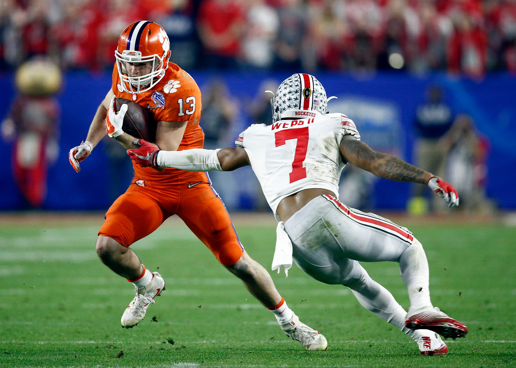 . Clemson wide receiver Hunter Renfrow (13) eludes Ohio State safety Damon Webb (7) during the first half of the Fiesta Bowl NCAA college football game, Saturday, Dec. 31, 2016, in Glendale, Ariz. (AP Photo/Ross D. Franklin)