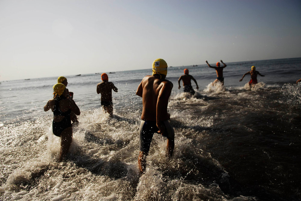 . Participants of the annual Paso del Hombre endurance challenge jump into the water at La Libertad port in El Salvador on February 24, 2013. About 370 male and female lifeguard volunteers swam for four to five hours continuously during the 49th edition of the event organized by the Salvadorian Red Cross in collaboration with the Navy, Coast Guard, Air Force and Civil National Police.  REUTERS/Ulises Rodriguez