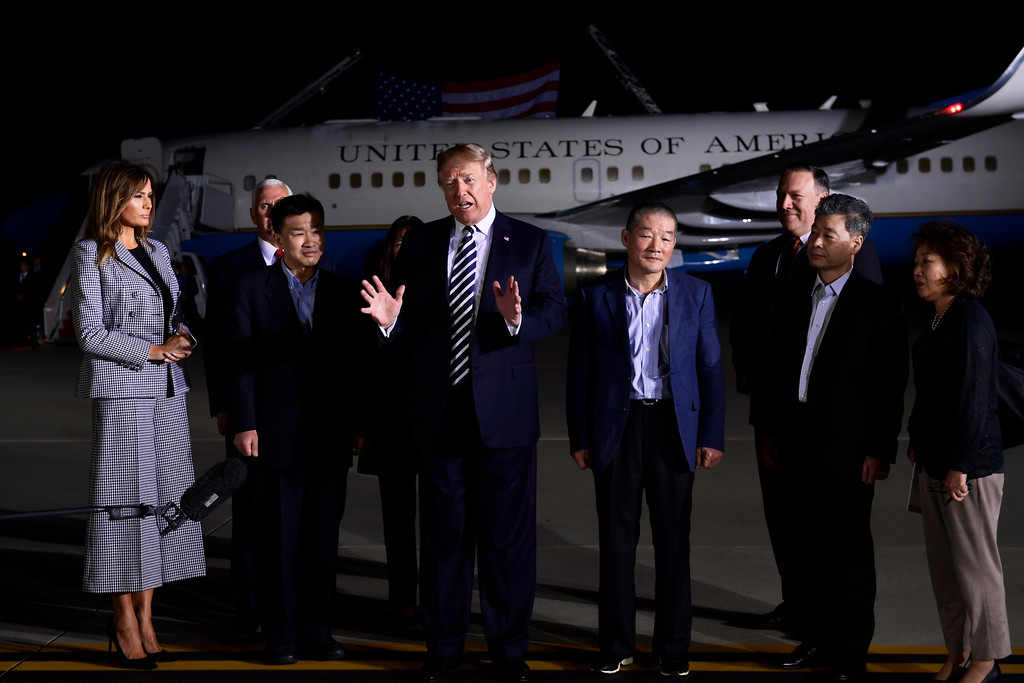 . President Donald Trump, center, speaks as he greets Tony Kim, third left, Kim Dong Chul, fourth right, and Kim Hak Song, second right, three Americans detained in North Korea for over a year, as they arrive at Andrews Air Force Base in Md., Thursday, May 10, 2018. First lady Melania Trump, far left, Vice President Mike Pence, behind Tony Kim, and his wife Karen Pence, behind Trump, and Secretary of State Mike Pompeo were also at the air force base to greet them. The woman at right is unidentified. (AP Photo/Susan Walsh)