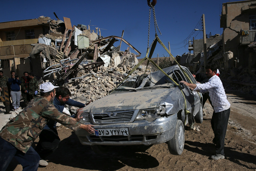 . People and rescuers move a destroyed car on the earthquake site in Sarpol-e-Zahab in western Iran, Tuesday, Nov. 14, 2017. Rescuers are digging through the debris of buildings felled by the Sunday earthquake in the border region of Iran and Iraq. (AP Photo/Vahid Salemi)