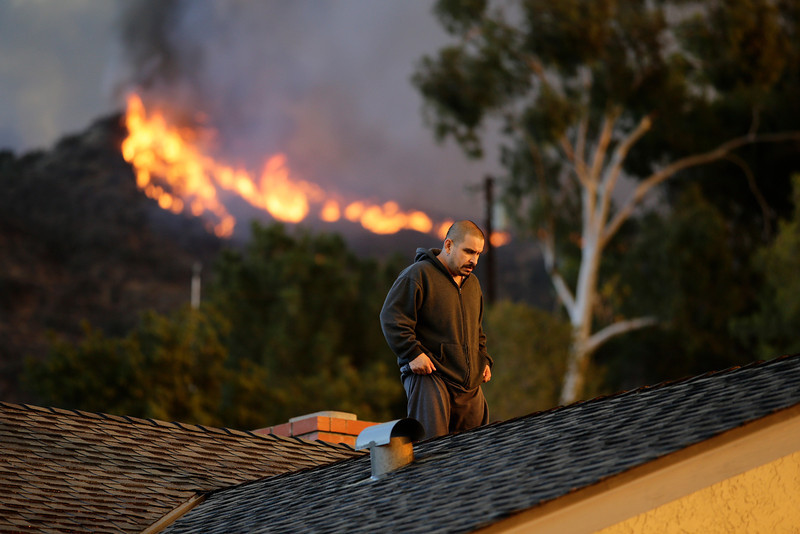 . A man walks off the rooftop after spraying water on his home as firefighters battle a wildfire on Thursday, Jan. 16, 2014, in Azusa, Calif. A wildfire burned out of control near homes in the dangerously dry foothills of the San Gabriel Mountains early Thursday, fanned by gusty Santa Ana winds that spit embers into neighborhoods in the city below, igniting trees. Evacuations were ordered for houses at the edge of the fire. (AP Photo/Jae C. Hong)