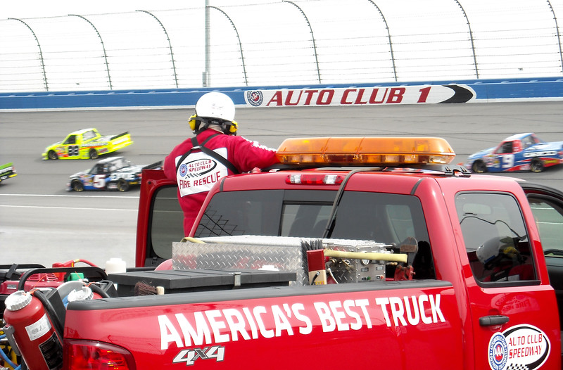 Fire Safety watch the NASCAR trucks round turn 1 at Autoclub speedway.