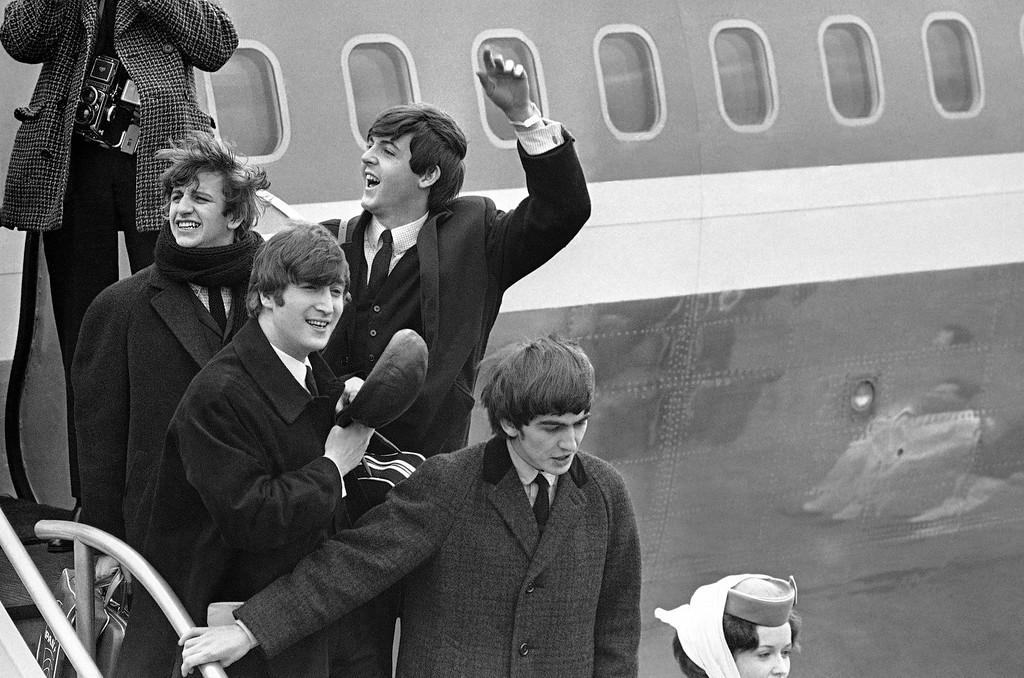 . Britain�s Beatles make a windswept arrival in New York on Feb. 7, 1964, as they step down from the plane that brought them from London, at Kennedy airport. From left to right, Ringo Starr, John Lennon, Paul McCartney and George Harrison (AP Photo)