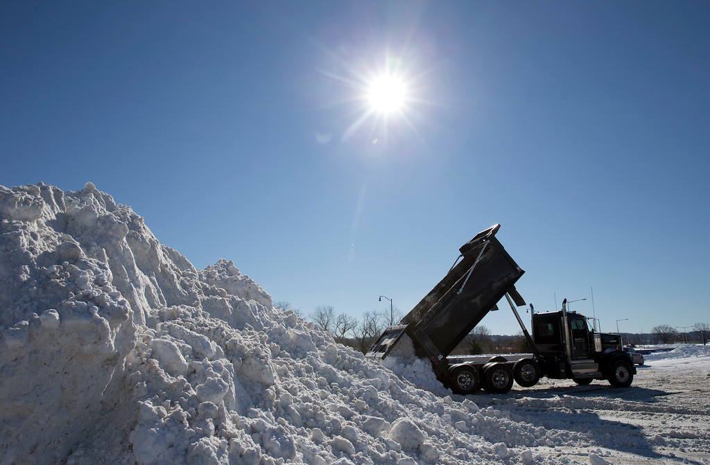 . Snow from around the Washington area is dumped in the parking lot of Robert F. Kennedy Memorial Stadium in Washington, Sunday, Jan. 24, 2016. Washington is digging out from mammoth blizzard with hurricane-force winds and record-setting snowfall brought much of the East Coast to an icy standstill. (AP Photo/Carolyn Kaster)