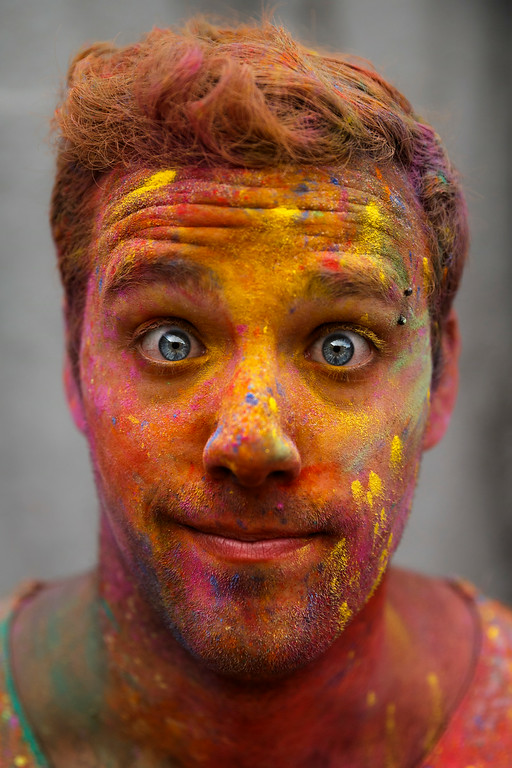 . A reveler poses for a picture with his face stained with special colored powders while taking part in the Holi Festival of Colors, in Madrid, Spain, Saturday, Aug. 9, 2014. (AP Photo/Daniel Ochoa de Olza)