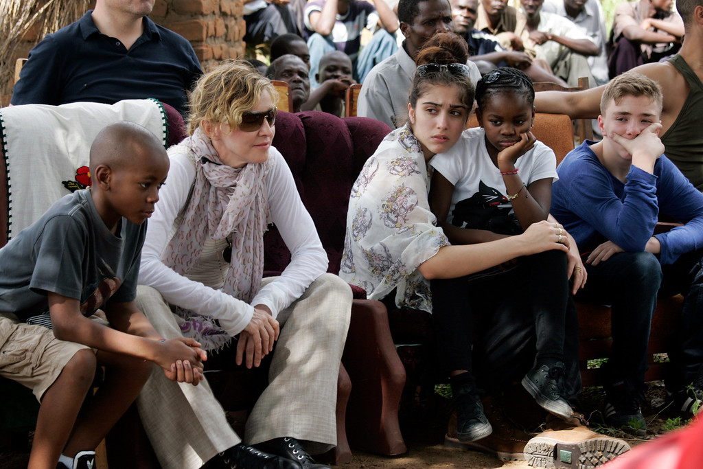 . US Pop Star Madonna (2nd L) sits with her biological and adopted children (L to R) David Banda, Lourdes, Mercy James, and Rocco at Mkoko Primary School, one of the schools Madonna\'s Raising Malawi organization has built jointly with US organization BuildOn, during the visit of Madonna on April 2, 2013 in the region of Kasungu, central Malawi. Madonna, said to be the single largest international philanthropic donor to Malawi, also supports childcare in the country which is home to nearly a million children orphaned by AIDS. She arrived in Malawi on March 31 with the two children she adopted from the small landlocked African country. AFP PHOTO / AMOS GUMULIRA