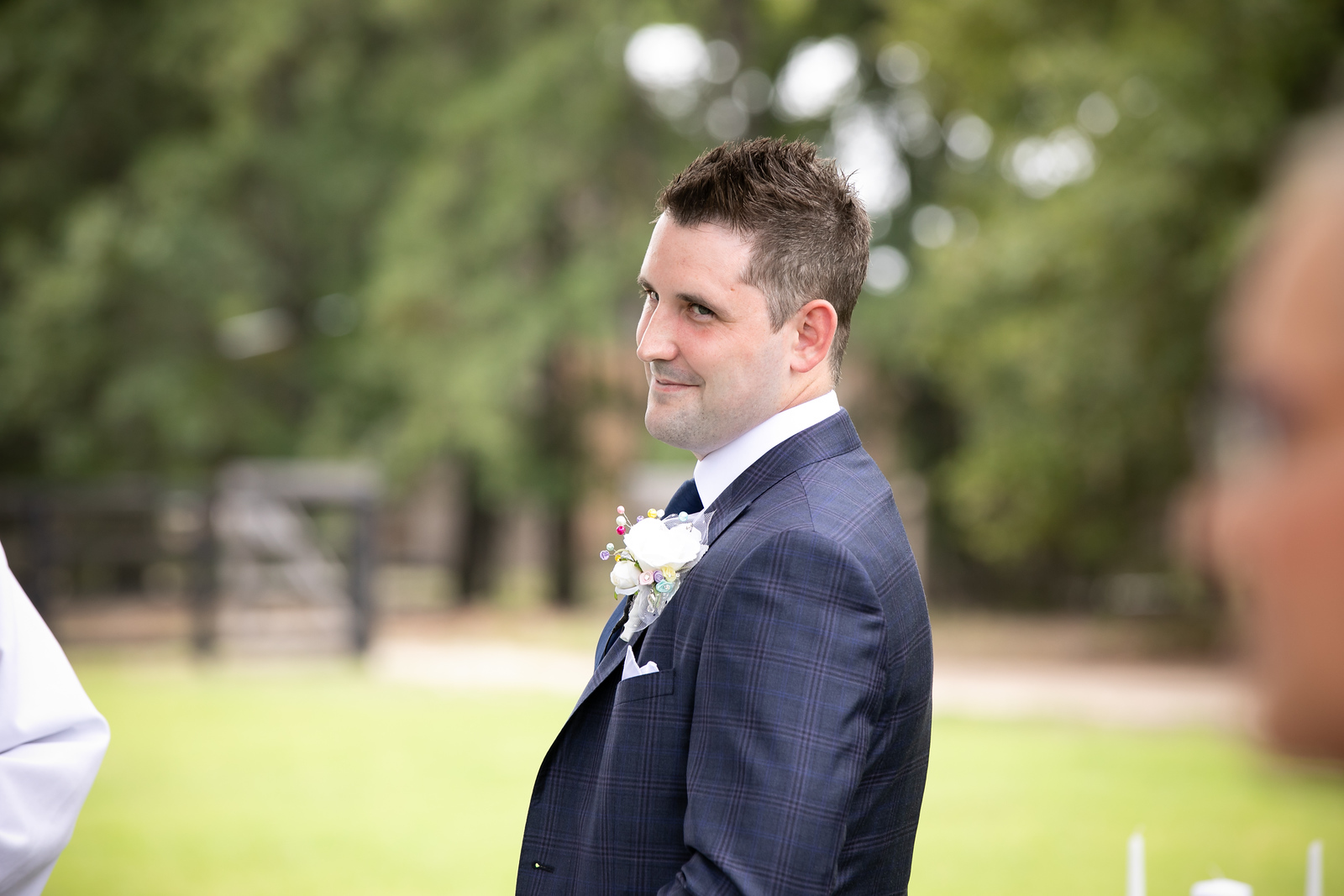 a groom standing at the altar smiling as he looks over his shoulder down the aisle