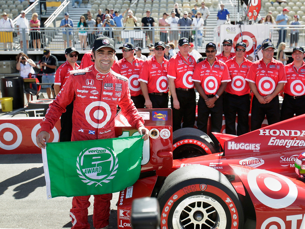 . Dario Franchitti, of Scotland, displays the flag he received for being the top qualifier for Sunday\'s IndyCar auto race, Saturday, Aug. 24, 2013 in Sonoma, Calif. (AP Photo/Rich Pedroncelli)