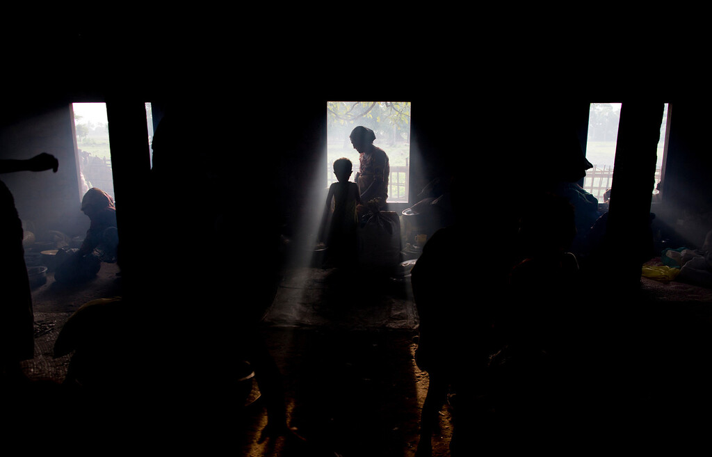 . Internally displaced Rohingya people taking refuge in a building belongs to a mosque are silhouetted in Sittwe, northwestern Rakhine State, Myanmar, ahead of the arrival of Cyclone Mahasen, Wednesday, May 15, 2013. A massive evacuation to clear low-lying camps ahead of a cyclone has run into a potentially deadly snag as members of the displaced Rohingya minority living there have refused to leave because they don\'t trust Myanmar authorities. (AP Photo/Gemunu Amarasinghe)