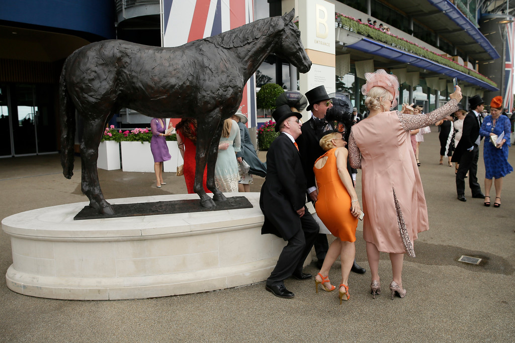 . Racegoers pose for a photo on the second day of the Royal Ascot horse race meeting in Ascot, England, Wednesday, June 20, 2018. (AP Photo/Tim Ireland)