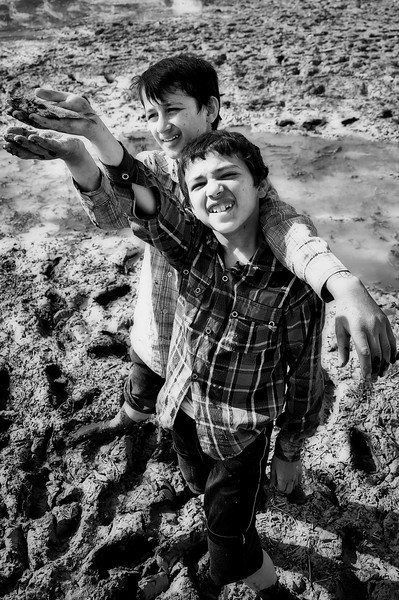 Young boys showing small fishes in their hands, Isfahan, Iran.