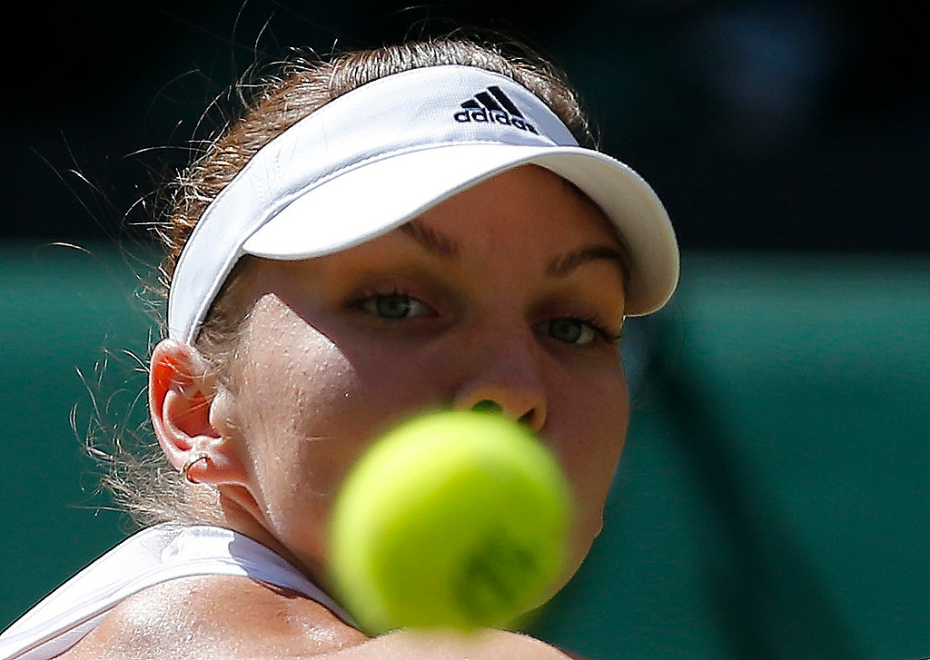 . Simona Halep of Romania keeps her eyes on the ball as she prepares to play a return to Eugenie Bouchard of Canada during their womenís singles semifinal match at the All England Lawn Tennis Championships in Wimbledon, London, Thursday, July 3, 2014. (AP Photo/Ben Curtis)