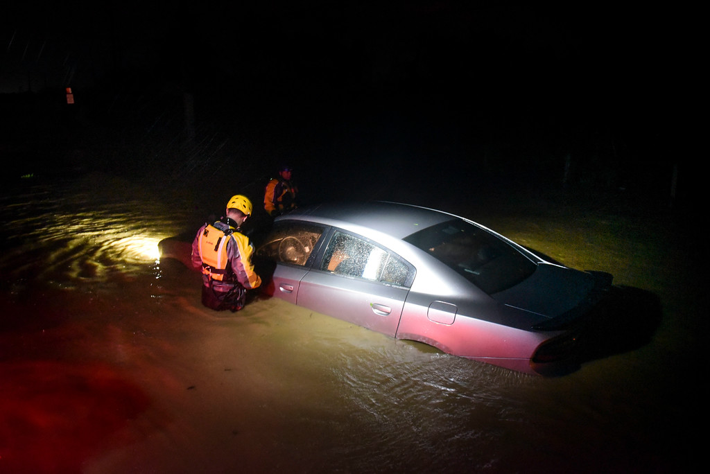 . Rescue staff from the Municipal Emergency Management Agency investigate an empty flooded car during the passage of Hurricane Irma through the northeastern part of the island in Fajardo, Puerto Rico, Wednesday, Sept. 6, 2017. Hurricane Irma lashed Puerto Rico with heavy rain and powerful winds, leaving nearly 900,000 people without power as authorities struggled to get aid to small Caribbean islands already devastated by the historic storm. (AP Photo/Carlos Giusti)