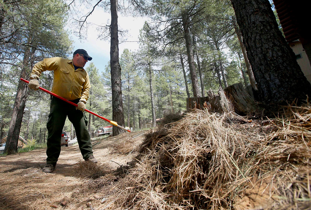 . John Rheinbolt, of the Western Defense Systems private contractor, works on pulling pine needles and other ground clutter away from a home as the Slide Fire burns nearby on Thursday, May 22, 2014, in Kachina Village, Ariz.   The fire, which has burned approximately 4,800 acres, is 3 to 3 1/2 miles away from the residential areas of Forest Highlands and Kachina Village, where the 3,200 residents remain under pre-evacuation warnings. (AP Photo/Ross D. Franklin)