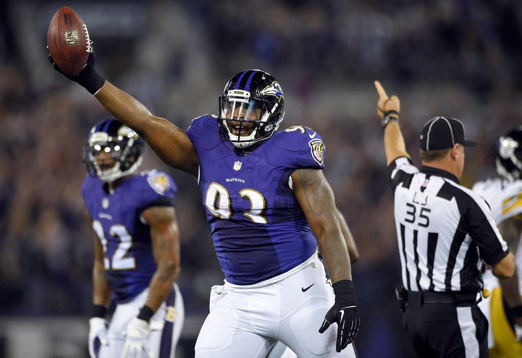 . Baltimore Ravens defensive end DeAngelo Tyson (93) holds up the ball after recovering a Pittsburgh Steelers fumble during the first half of an NFL football game Thursday, Sept. 11, 2014, in Baltimore. (AP Photo/Nick Wass)