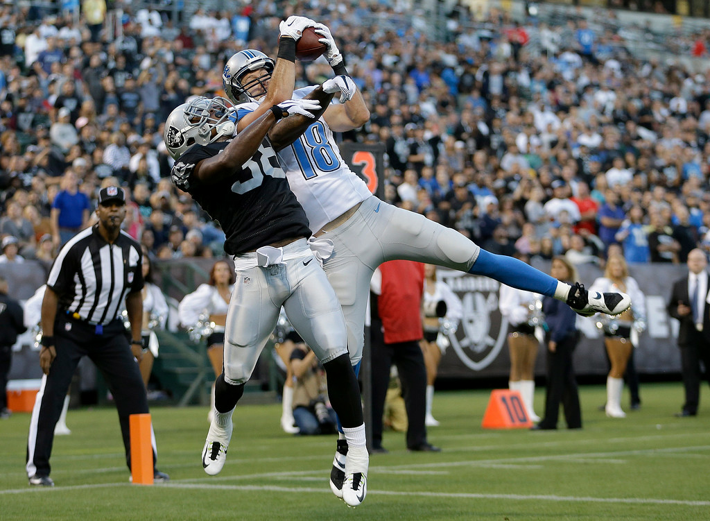 . Detroit Lions wide receiver Kris Durham (18) catches a 4-yard touchdown pass over Oakland Raiders cornerback T.J. Carrie (38) during the first quarter of an NFL preseason football game in Oakland, Calif., Friday, Aug. 15, 2014. (AP Photo/Ben Margot)