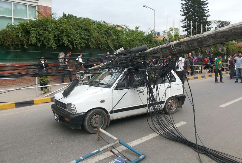 . A car stands under the weight of an electric pole after it collapsed following an earthquake in Kathmandu, Nepal, Saturday, April 25, 2015. A strong magnitude-7.9 earthquake shook Nepal\'s capital and the densely populated Kathmandu Valley before noon Saturday, causing extensive damage with toppled walls and collapsed buildings, officials said. A magnitude-6.6 aftershock hit about an hour later, and smaller aftershocks continued to ripple through the region for hours. (AP Photo/Tashi Sherpa)