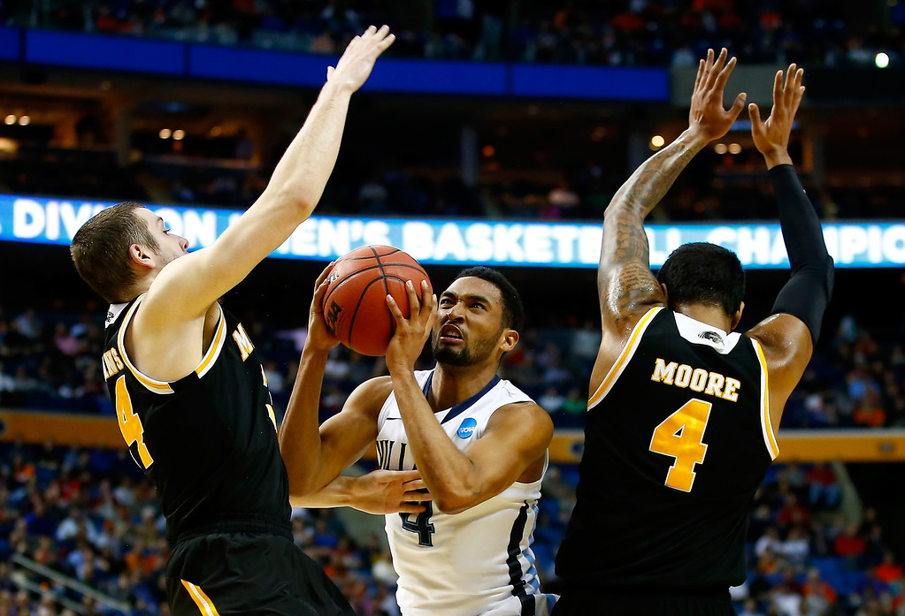 . BUFFALO, NY - MARCH 20:  Darrun Hilliard II #4 of the Villanova Wildcats goes to the basket as Austin Arians #34 and Malcolm Moore #4 of the Milwaukee Panthers defend during the second round of the 2014 NCAA Men\'s Basketball Tournament at the First Niagara Center on March 20, 2014 in Buffalo, New York.  (Photo by Jared Wickerham/Getty Images)