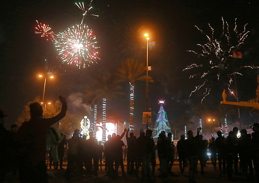 . Iraqis watch fireworks explode during the New Year\'s Day celebrations in Baghdad, Iraq, early Monday, Jan. 1, 2018. (AP Photo/Khalid Mohammed)