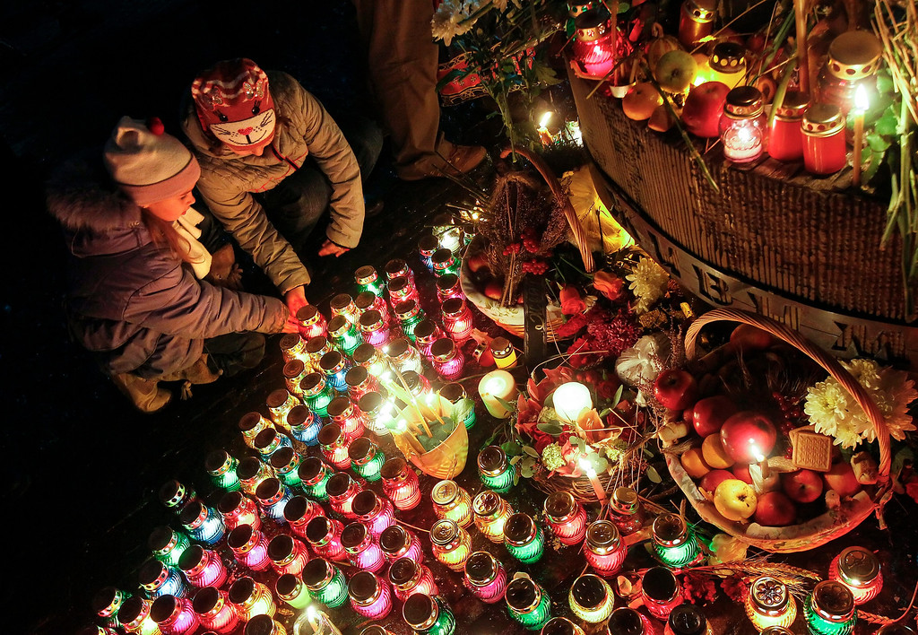 . Ukrainian children light candles during a memorial ceremony near of a monument to the victims of the Great Famine in Kiev, 23 November 2013. Reports state that Ukrainians light candles to mark a day of memory for the victims of the Holodomor in 1932-1933.   EPA/SERGEY DOLZHENKO