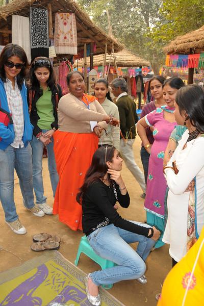 Girls getting their hair braided at the Suraj Kund Mela 2009 held in Haryana (outskirts of Delhi), North India.   The Suraj Kund Mela is an annual fair held near Delhi. Folk dances, handicrafts and a lot of fun.