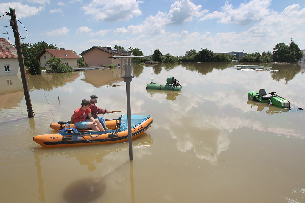 . A man and a boy in a rubber boat make their way through the flooded village of Deggendorf, southern Germany, on June 5, 2013.     AFP PHOTO / KARL-JOSEF HILDENBRAND /AFP/Getty Images