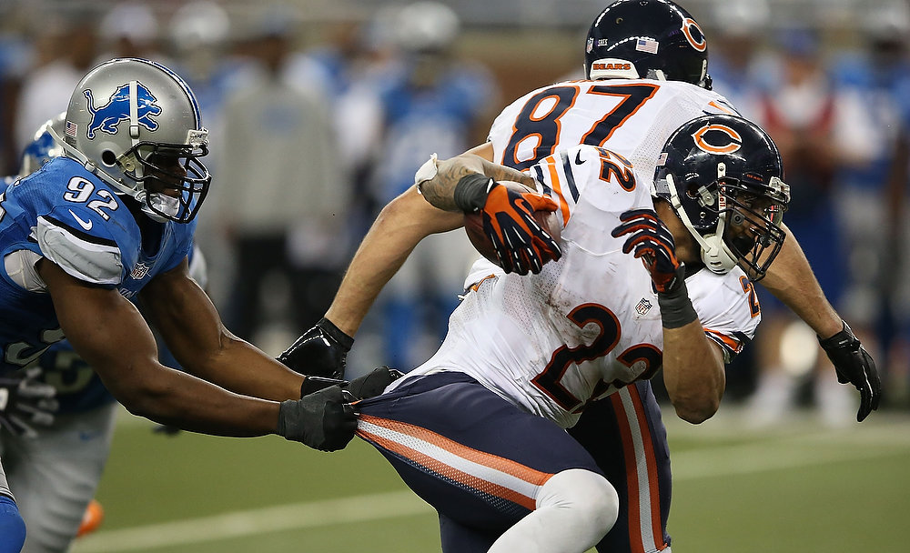 . Matt Forte #22 of the Chicago Bears runs for a short gain during the fourth quarter as Cliff Avril #92 of the Detroit Lions attempts to make the stop during the game at Ford Field on December 30, 2012 in Detroit, Michigan. The Bears defeted the Lions 26-24.  (Photo by Leon Halip/Getty Images)