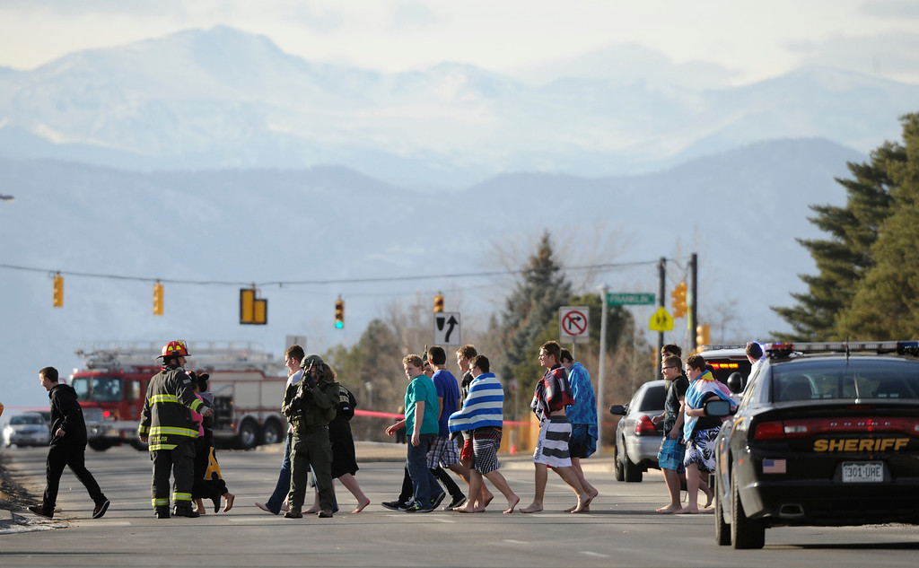 . LITTLETON, CO - DECEMBER 13 : At the school shooting at Arapahoe High School in Centennial, CO  on Friday, December 13, 2013  students are escorted across  Dry Creek Road with mountains in back. (Photo By Cyrus McCrimmon/The Denver Post)