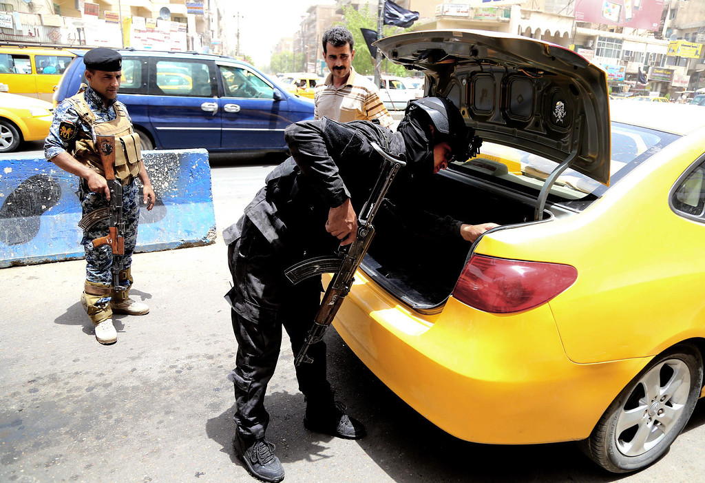 . An Iraqi federal policeman stands guard as his colleague searches a car at a checkpoint in Baghdad, Iraq, Wednesday, June. 11, 2014. The Iraqi government has tightened its security measures after a stunning assault that exposed Iraq\'s eroding central authority, al-Qaida-inspired militants overran much of Mosul on Tuesday, seizing government buildings, pushing out security forces and capturing military vehicles as thousands of residents fled the Iraqi second-largest city. (AP Photo/ Karim Kadim)
