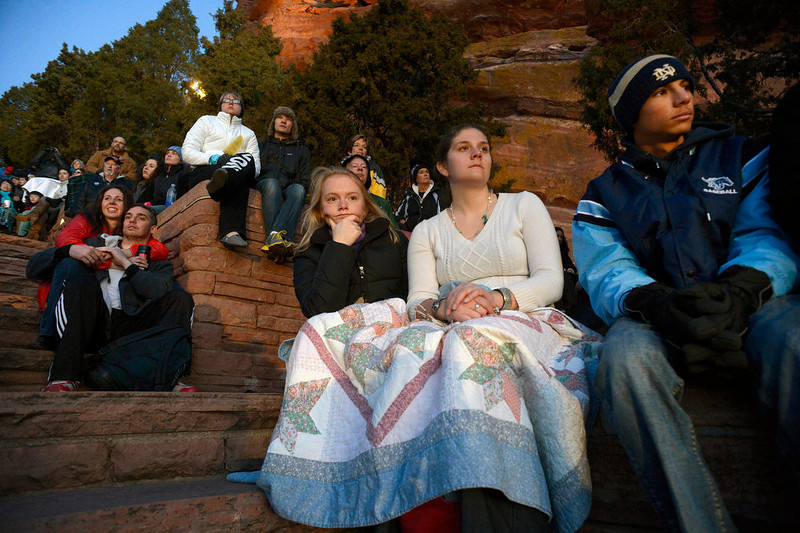 . From right to left Jacob Schaefer, of Arvada, Brittany Mosher, and Kristen Davenport, both of Fort Collins, listen to the service. Thousands of people turned out for the sixty sixth annual Easter sunrise service at Red Rocks Amphitheatre in Golden on March 31st, 2013.The sun rose at 6:45 am under cloudless skies and this year\'s service was pleasant with warmer temperatures than in previous years.  The service, sponsored by the Colorado Council of Churches, was led by Reverend Dr. Jim Ryan and presided over by Reverend Dr. Janet Forbes.  (Photo By Helen H. Richardson/ The Denver Post)
