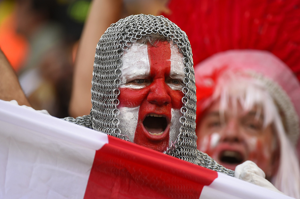 . An England fan with his face painted in the colours of his national flag and wearing a chain mail costume cheers prior to a Group D football match between England and Italy at the Amazonia Arena in Manaus during the 2014 FIFA World Cup on June 14, 2014. AFP PHOTO / FABRICE COFFRIN