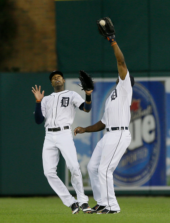 . Detroit Tigers center fielder Austin Jackson, left, and right fielder Torii Hunter, right, nearly collide as Hunter catches the fly out hit by Chicago White Sox\'s Alejandro De Aza during the third inning of a baseball game, Wednesday, July 30, 2014 in Detroit. (AP Photo/Carlos Osorio)