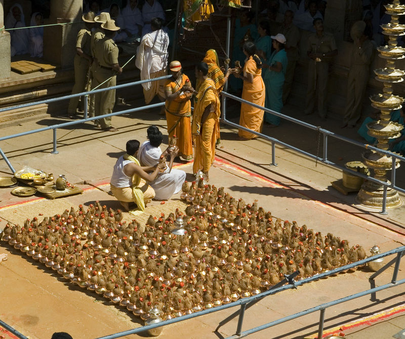 Copper pots of water are handed out as offerings. They are taken to the top and poured over the Gomatheswar.