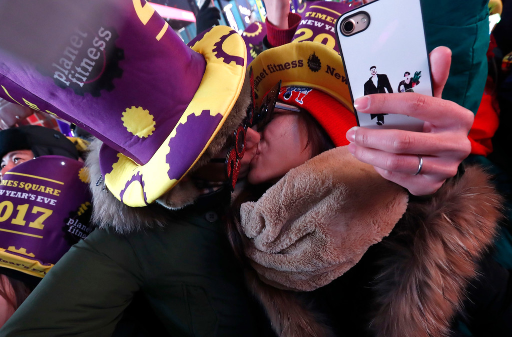. Mikito Horino, left, and kisses his wife, Taki Horino, from Japan, during a new years celebration at Times Square, Sunday, Jan. 1, 2017, in New York. (AP Photo/Julio Cortez)