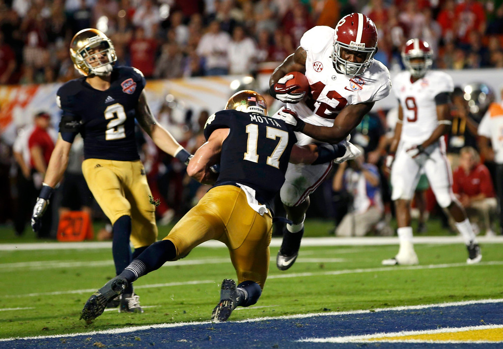 . Alabama Crimson Tide running back Eddie Lacy (42) scores a touchdown past Notre Dame Fighting Irish safety Zeke Motta and cornerback Bennett Jackson (2) during the second quarter of their NCAA BCS National Championship college football game in Miami, Florida, January 7, 2013. REUTERS/Mike Segar