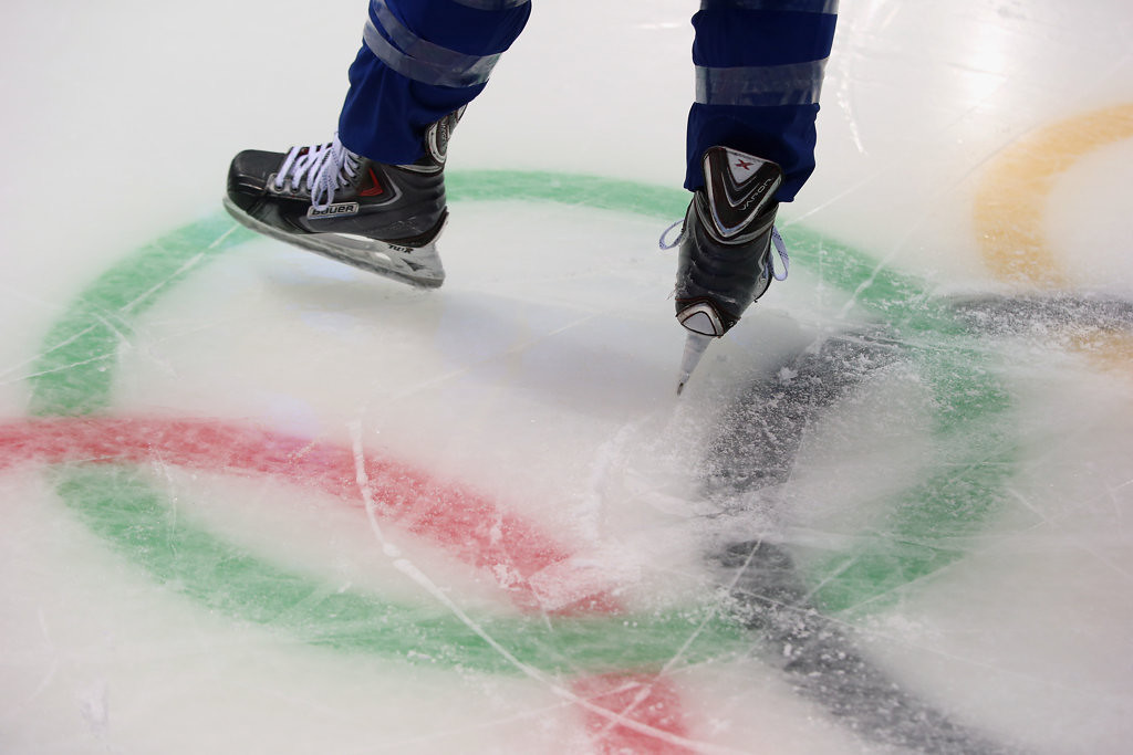 . A member of the United States women\'s ice hockey team skates over the Olympic rings logo.  (Getty Images: Bruce Bennett)