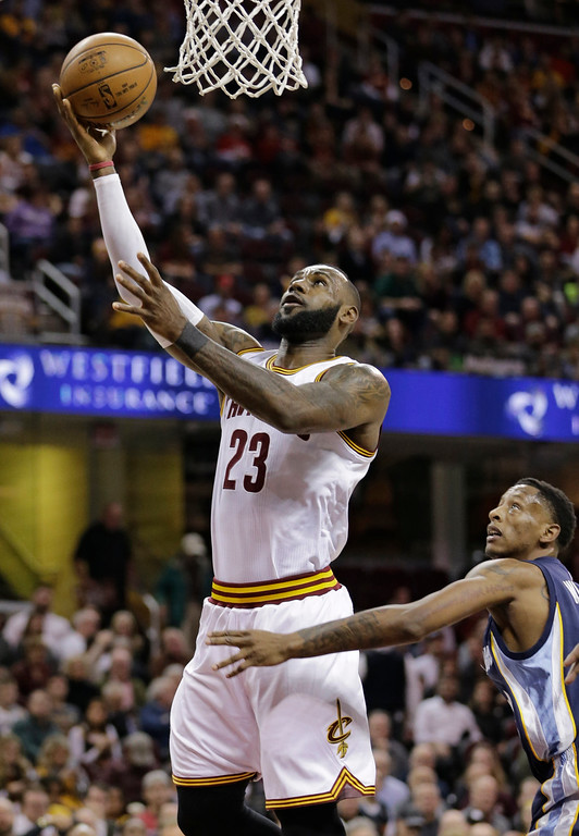 . Cleveland Cavaliers\' LeBron James (23) shoots over Memphis Grizzlies\' Troy Williams (10) in the first half of an NBA basketball game Tuesday, Dec. 13, 2016, in Cleveland. (AP Photo/Tony Dejak)