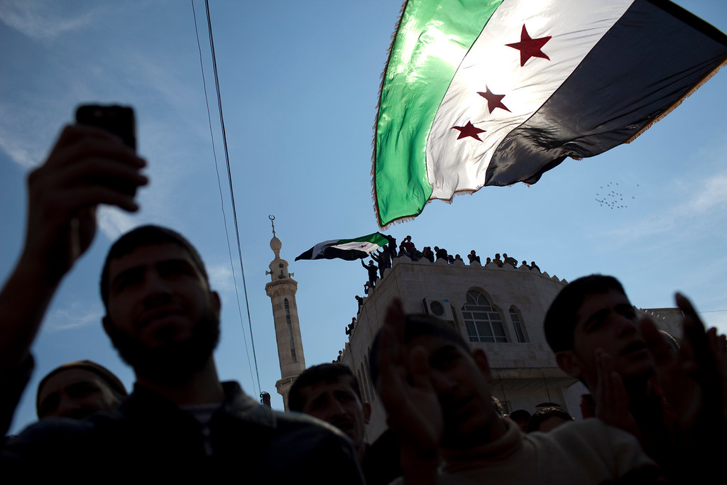 . In this Friday, March 2, 2012 file photo, men hold revolutionary Syrian flags during an anti government protest in a town in north Syria. More than two years into Syria\'s civil war, the once highly-centralized authoritarian state has effectively split into three distinct parts, each boasting its own flags, security agencies and judicial system. (AP Photo/Rodrigo Abd)