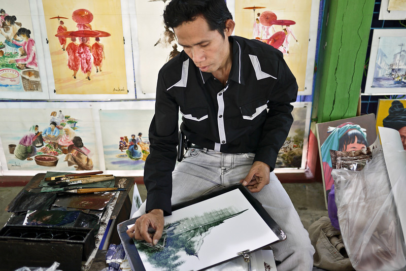 A craftsman makes a quick oil painting with a razor blade on the top of Mandalay Hill.