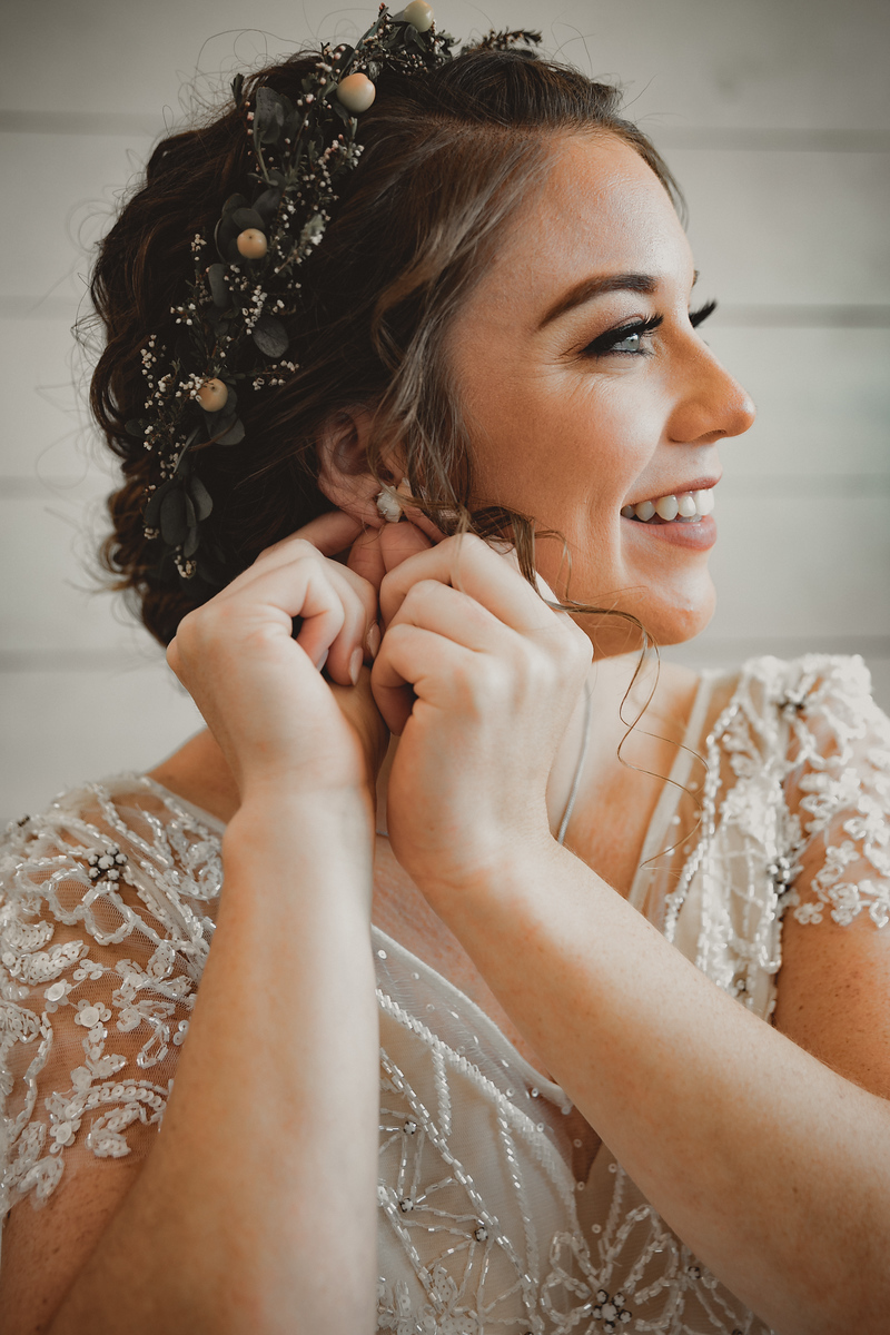 A bride wearing a lace wedding dress putting in her earings just before her wedding ceremony
