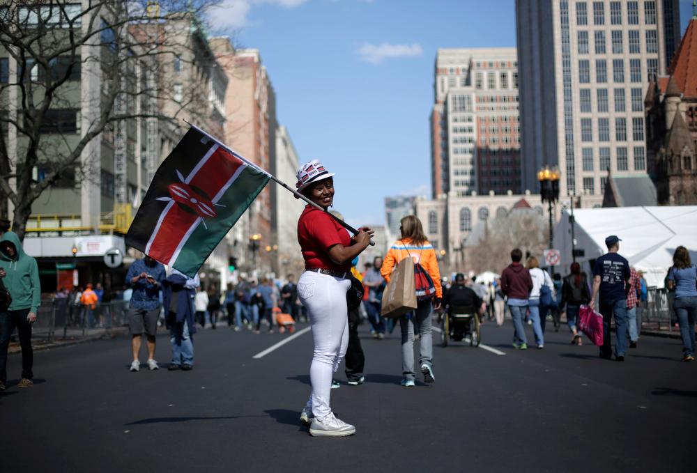 . Sallie Wambui, of Kenya, displays her country\'s flag Saturday, April 19, 2014, along Boylston Street in Boston, in advance of Monday\'s 118th Boston Marathon. (AP Photo/Robert F. Bukaty)