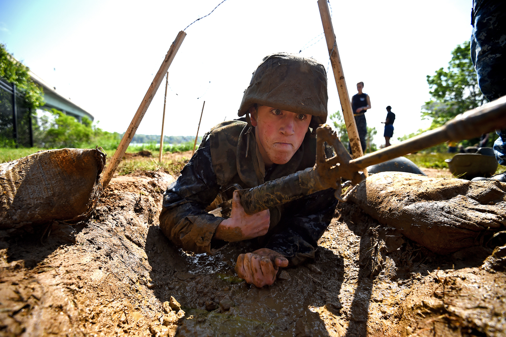 . A member of the United States Naval Academy freshman class crawls through trenches at the wet and sandy station during the annual Sea Trials training exercise at the U.S. Naval Academy on May 13, 2014 in Annapolis, Maryland. (Photo by Patrick Smith/Getty Images)