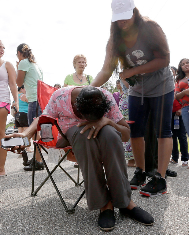 . A woman, who did not wish to be identified, is consoled after hearing the name of the victim as she waits across the street from Spring High School Wednesday, Sept. 4, 2013, in Spring, Texas. (AP Photo/David J. Phillip)