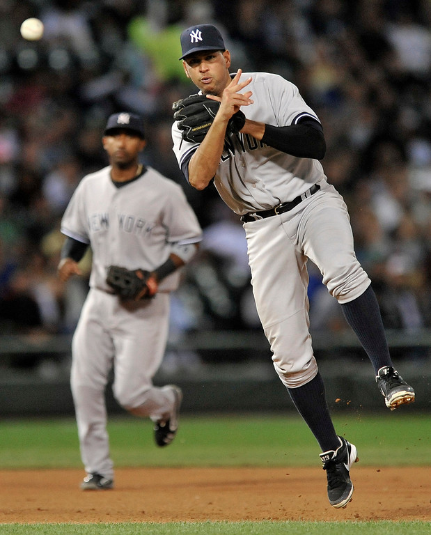 . New York Yankees third baseman Alex Rodriguez, right, throws to first base during the sixth inning of a baseball game against the Chicago White Sox in Chicago, Monday, Aug. 5, 2013. (AP Photo/Paul Beaty)