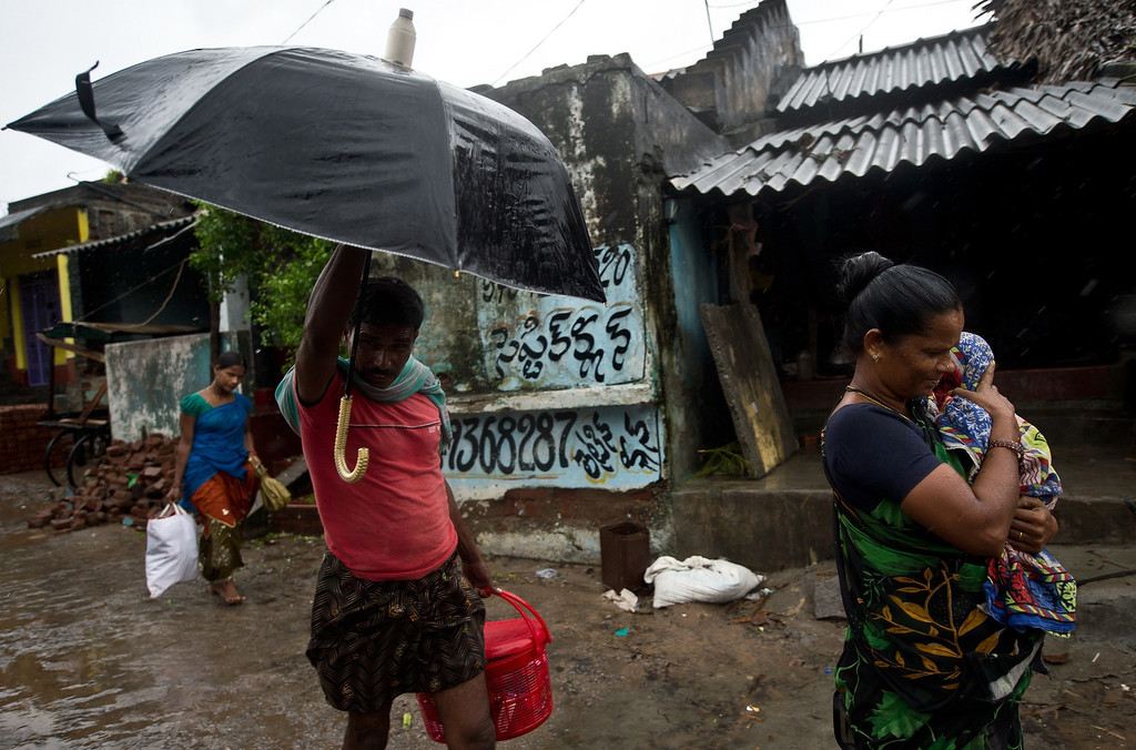 . An Indian resident carries her child as she leaves her home in Donkuru village in Srikakulam district on October 12, 2013. India evacuated nearly half a million people as massive cyclone Phailin closed in on the impoverished east coast, with winds already uprooting trees and tearing into the flimsy homes.  MANAN VATSYAYANA/AFP/Getty Images